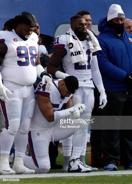 Damon Harrison and Landon Collins of the New York Giants rest their hands on teammate Olivier Vernon as Vernon kneels during the national anthem...