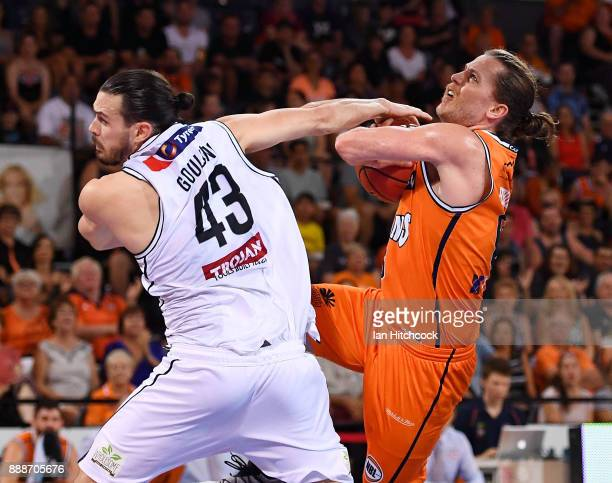 Damon Heir of the Taipans is blocked by Chris Goulding of Melbourne United during the round nine NBL match between the Cairns Taipans and Melbourne...