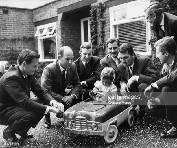 Damon Hill 10 mois le jour de son baptême au volant d'une voiture miniature entouré de Bruce McLaren Stirling Moss Tony Brooks Graham Hill Joakim...