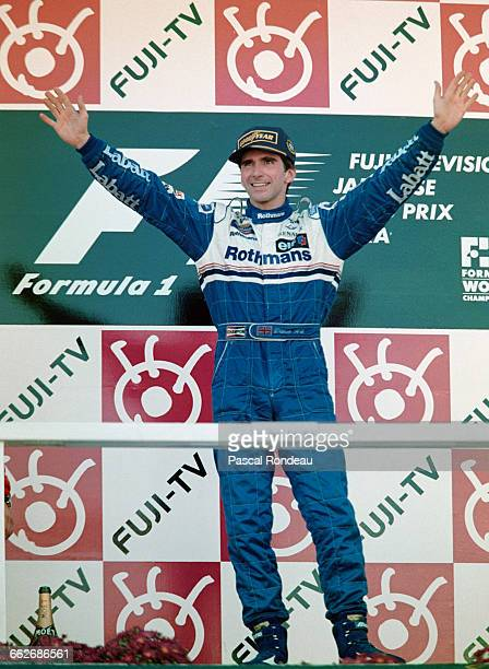 Damon Hill of Great Britain and driver of the Rothmans Williams Renault Williams FW18 Renault RS8 V10 celebrates winning the race and the World...