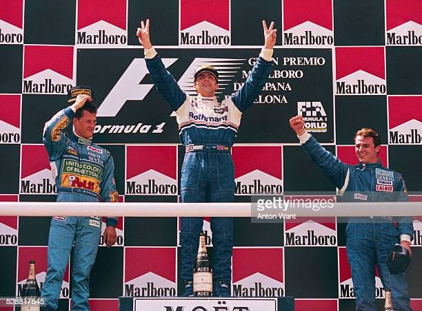 Damon Hill of Great Britain, driver of the Rothmans Williams Renault Williams FW16B Renault V10 celebrates on the podium with second placed Michael...