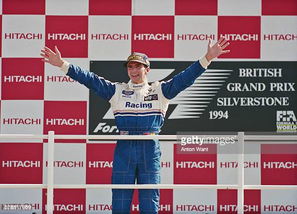 Damon Hill of Great Britain, driver of the Rothmans Williams Renault Williams FW16B Renault V10 celebrates winning the British Grand Prix on 10th...