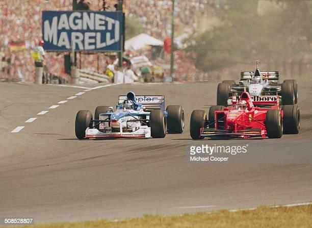 Damon Hill of Great Britain drives the Danka Arrows Yamaha Arrows A18 Yamaha 0X11A V10 ahead of Michael Schumacher at the start of the Hungarian...
