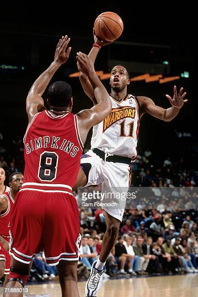 Damon Jones of the Golden State Warriors shoots a layup against Dickey Simpkins of Chicago Bulls during a game at the Arena in Oakland on November 16...
