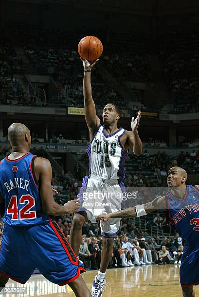 Damon Jones of the Milwaukee Bucks puts up a layup between Vin Baker and Stephon Marbury of the New York Knicks during the game on March 14 2004 at...