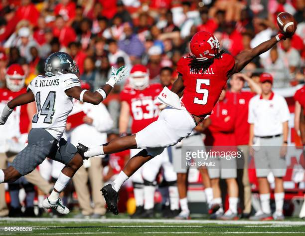 Damon Mitchell of the Rutgers Scarlet Knights reaches for the ball but can't make the catch as Ross Williams of the Eastern Michigan Eagles defends...