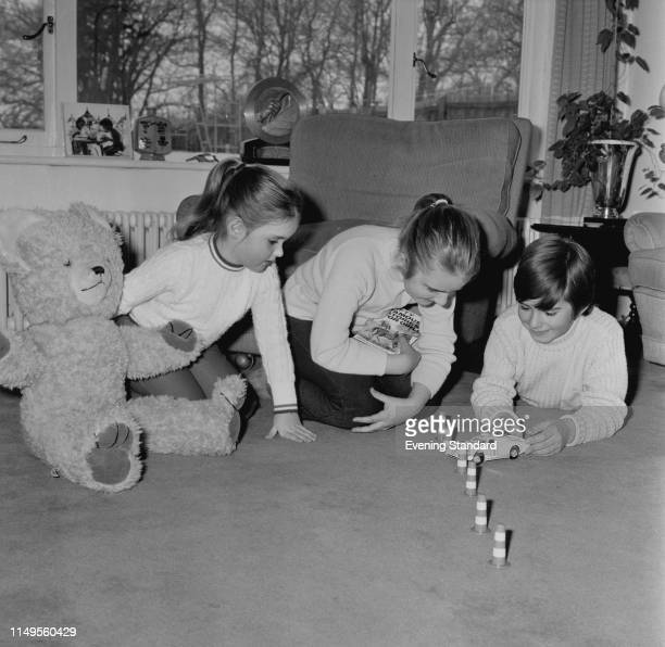 Damon, Samantha and Brigitte Hill, the children of British racing driver Graham Hill and Bette Hill, playing together in a living room, UK, 7th March...