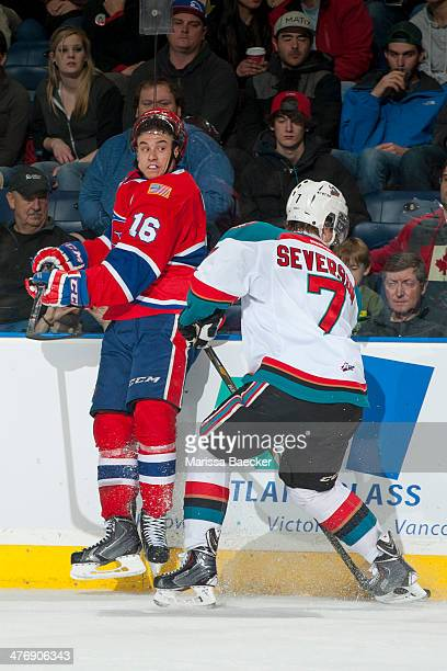 Damon Severson of the Kelowna Rockets checks Mike Aviani of the Spokane Chiefs into the boards during second period on March 5, 2014 at Prospera...