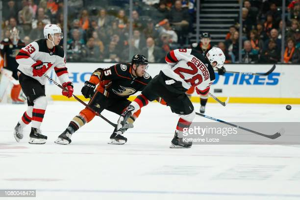 Damon Severson of the New Jersey Devils and Ondrej Kase of the Anaheim Ducks reach for the puck at Honda Center on December 09 2018 in Anaheim...