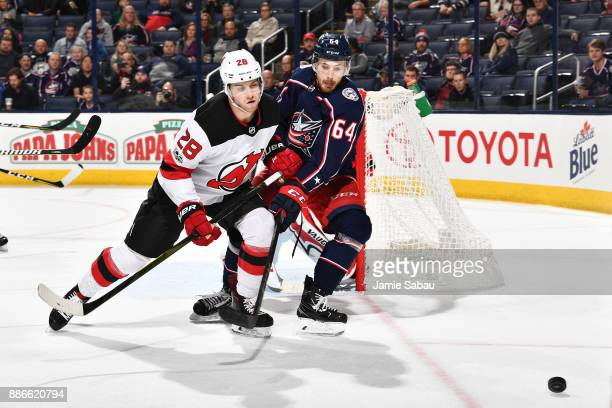 Damon Severson of the New Jersey Devils and Tyler Motte of the Columbus Blue Jackets battle for position as they skate after a loose puck during the...