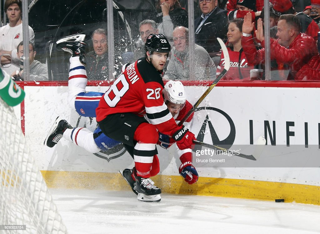 Damon Severson #28 of the New Jersey Devils checks Alex Galchenyuk #27 of the Montreal Canadiens into the board during the third period at the Prudential Center on March 6, 2018 in Newark, New Jersey. The Devils defeated the Canadiens 6-4.