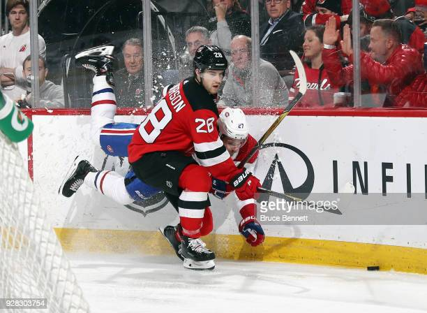 Damon Severson of the New Jersey Devils checks Alex Galchenyuk of the Montreal Canadiens into the board during the third period at the Prudential...