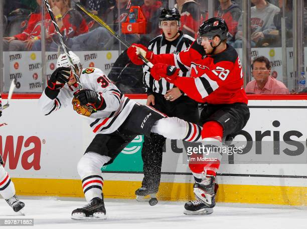 Damon Severson of the New Jersey Devils checks Ryan Hartman of the Chicago Blackhawks on December 23 2017 at Prudential Center in Newark New Jersey
