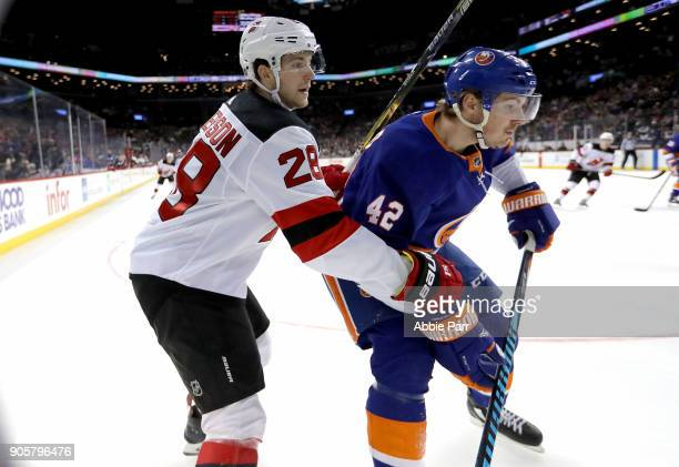 Damon Severson of the New Jersey Devils fights for the puck against Scott Mayfield of the New York Islanders in the second period during their game...