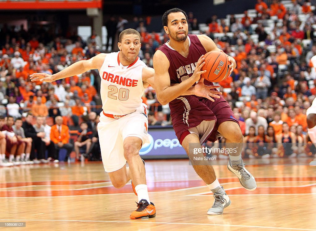 Damon Sherman-Newsome #21 of the Colgate Raiders drives the ball down the court against Brandon Triche #20 of the Syracuse Orange during the game at the Carrier Dome on November 25, 2012 in Syracuse, New York.