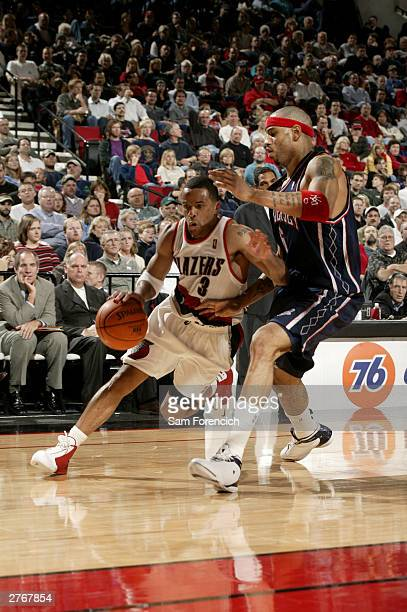 Damon Stoudamire of the Portland Trail Blazers drives past Kenyon Martin of the New Jersey Nets on November 28 2003 at the Rose Garden Arena in...