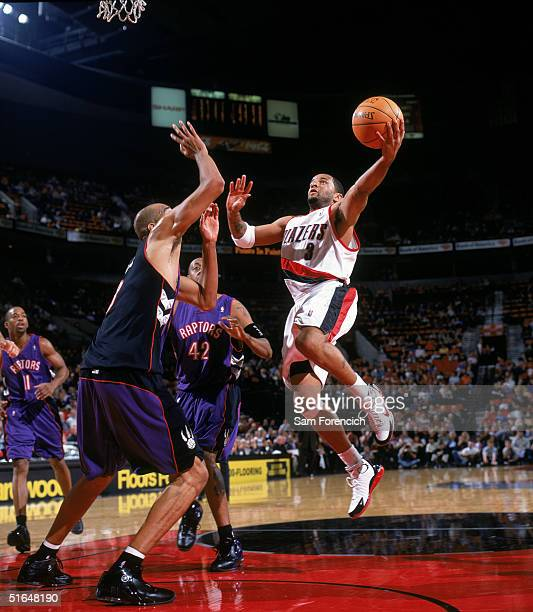 Damon Stoudamire of the Portland Trail Blazers drives to the basket for a layup against Loren Woods of the Toronto Raptors during a preseason game at...