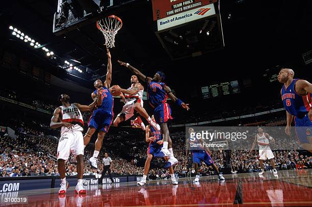 Damon Stoudamire of the Portland Trail Blazers shoots a layup over Ben Wallace and Corliss Williamson of the Detroit Pistons at The Rose Garden on...