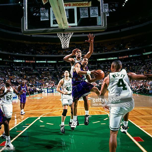 Damon Stoudamire of the Toronto Raptors drives against Rick Fox of the Boston Celtics during a game at the Fleet Center on December 11 1996 in Boston...