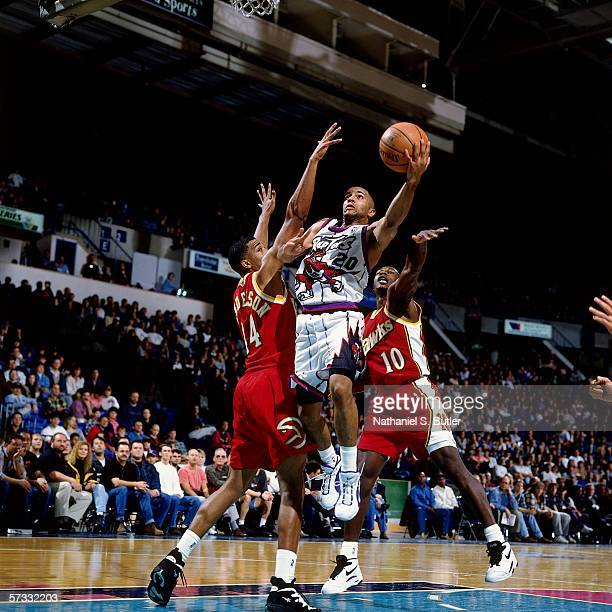 Damon Stoudamire of the Toronto Raptors shoots against Allan Henderson of the Atlanta Hawks during a game at the Air Canada Centre on October 19 1995...