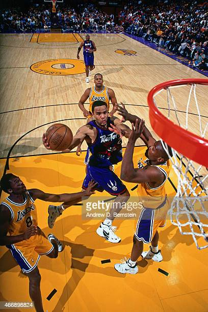 Damon Stoudamire of the Toronto Raptors shoots against Kobe Bryant of the Los Angeles Lakers on November 30 1997 at The Forum in Inglewood California...