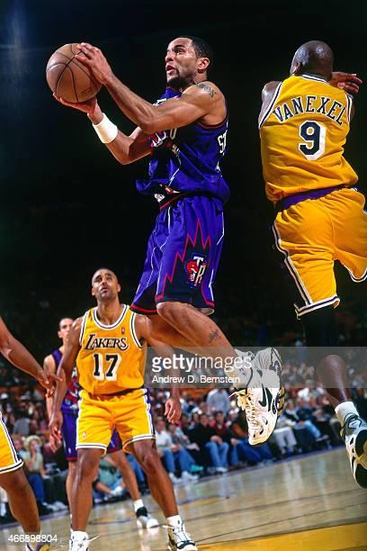 Damon Stoudamire of the Toronto Raptors shoots against Nick Van Exel of the Los Angeles Lakers on November 30 1997 at The Forum in Inglewood...