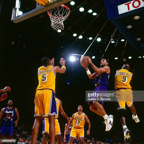 Damon Stoudamire of the Toronto Raptors shoots against Robert Horry and Nick Van Exel of the Los Angeles Lakers on November 30 1997 at The Forum in...