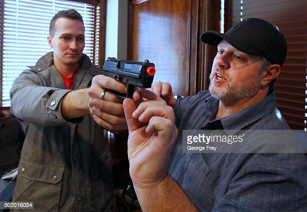 Damon Thueson shows Joel Zae how to hold a gun at a gun concealed carry permit class put on by USA Firearms Training on December 19 2015 in Provo...