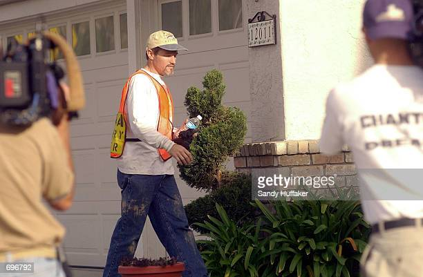 Damon van Dam walks towards his home after searching in local canyons for his missing daughter Danielle February 12 2002 in Sabre Springs near San...
