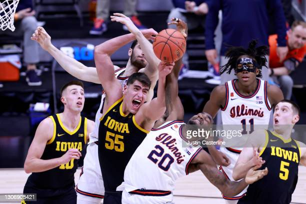 Da'Monte Williams of the Illinois Fighting Illini and Luka Garza of the Iowa Hawkeyes fight for the rebound during the second half of the Big Ten...