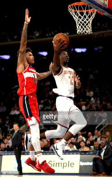 Damyean Dotson of the New York Knicks takes a shot against Kelly Oubre Jr #12 of the Washington Wizards in the second half during their Pre Season...