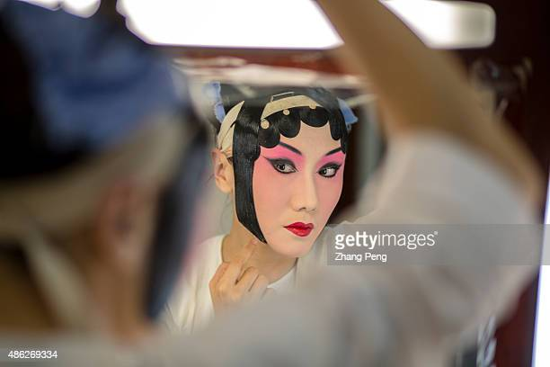 Dan actress is pasting Tiepian on the forehead and sideburns which is the second step in makeup Tiepian will change the natural look of the players...