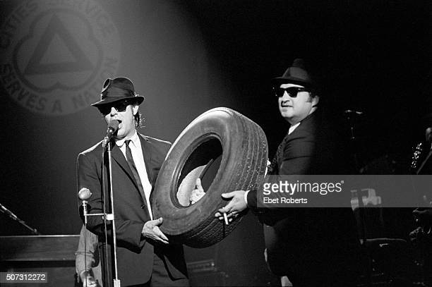 Dan Aykroyd and John Belushi holding a tyre and performing with The Blues Brothers at the Palladium in New York City on June 1 1980