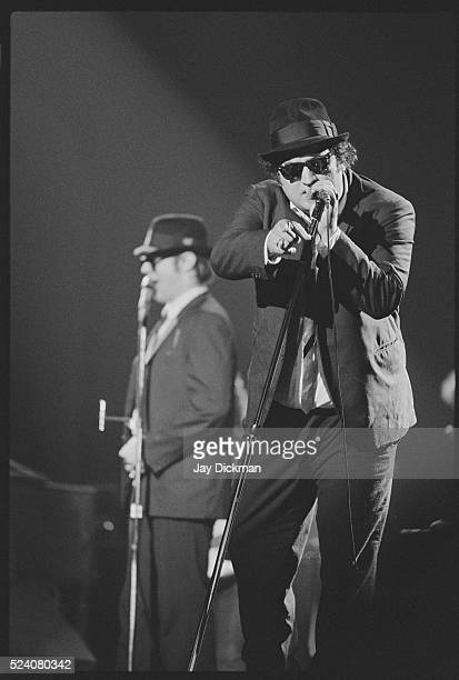 Dan Aykroyd and John Belushi performing on stage as the Blues Brothers