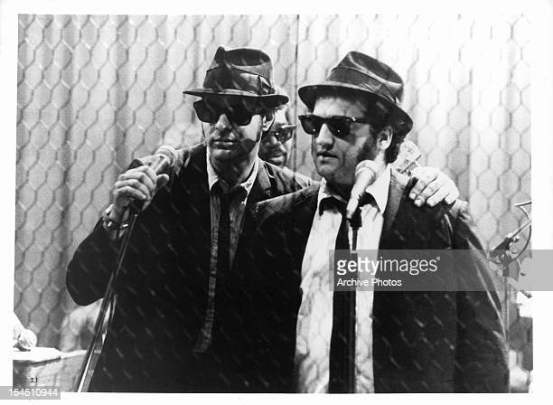 Dan Aykroyd holds a microphone standing next to John Belushi in a scene from the film 'The Blues Brothers' 1980