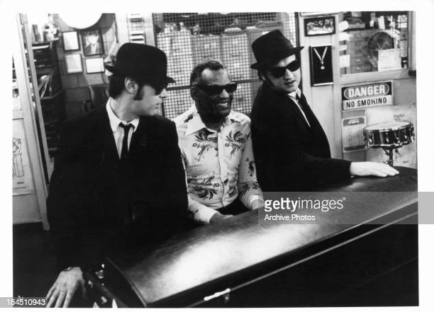 Dan Aykroyd listens as Ray Charles plays piano next to John Belushi in a scene from the film 'The Blues Brothers' 1980