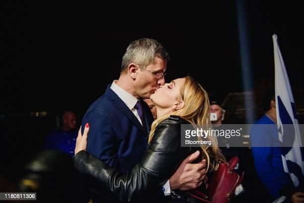 Dan Barna, leader of Save Romania Union and presidential candidate, left, kisses his wife, Olguta Dana Tolici, during a presidential election...