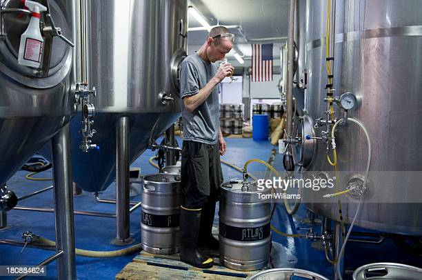 Dan Bedford a brewer for Atlas Brew Works on West Virginia Avenue NE samples a District Common beer while filling kegs at the brewery