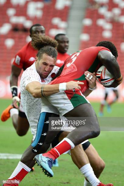 Dan Bibby of England challenges Oscar Oumo of Kenya during the 2018 Singapore Sevens Pool B match between Kenya and England at National Stadium on...
