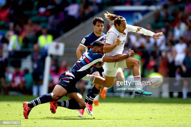 Dan Bibby of England kicks the ball away from Martin Iosefo of the USA on day one of the HSBC London Sevens at Twickenham Stadium on June 2 2018 in...
