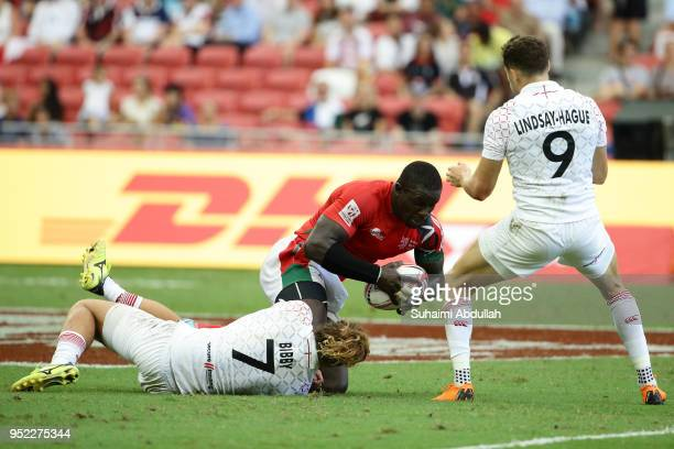 Dan Bibby of England tackles Andrew Amonde of Kenya during the 2018 Singapore Sevens Pool B match between Kenya and England at National Stadium on...
