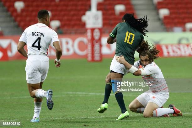 Dan Bibby of England tackles Cecil Afrika of South Africa during the 2017 Singapore Sevens match between South Africa and England at National Stadium...