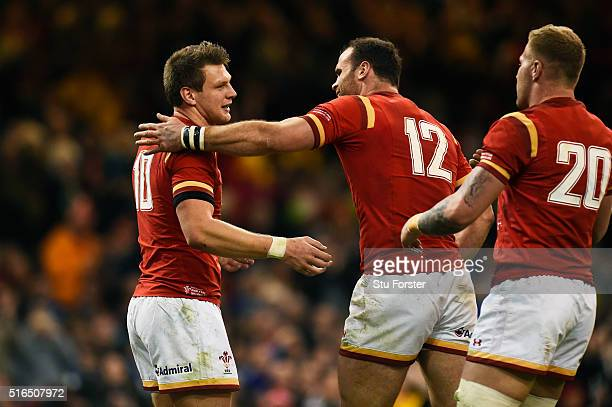 Dan Biggar of Wales is congratulated by teammate Jamie Roberts and Ross Moriarty after scoring his team's second try during the RBS Six Nations match...