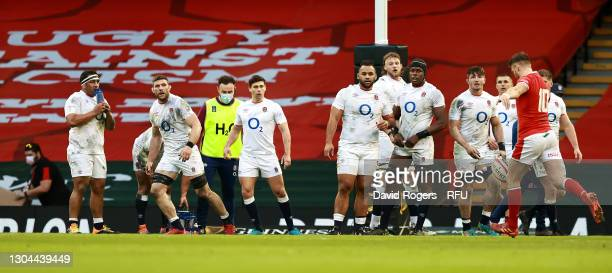 Dan Biggar of Wales kicks the ball to the corner to set up the first try for his team scored by Josh Adams as the England players look on during the...
