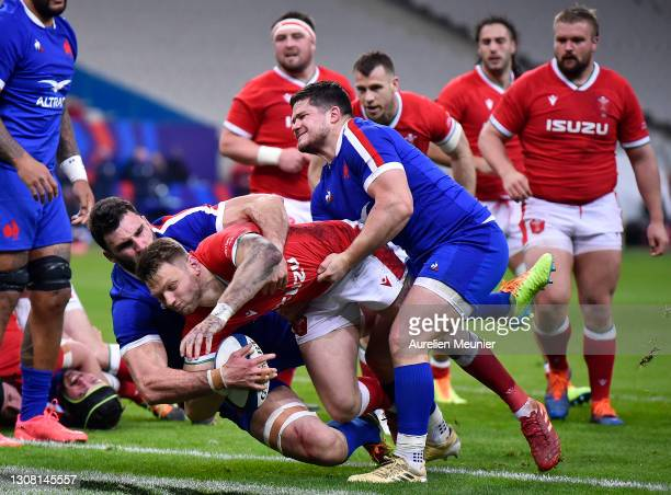 Dan Biggar of Wales scores his sides 1st try as Charles Ollivon and Julien Marchand of France attempt to tackle during the Guinness Six Nations match...