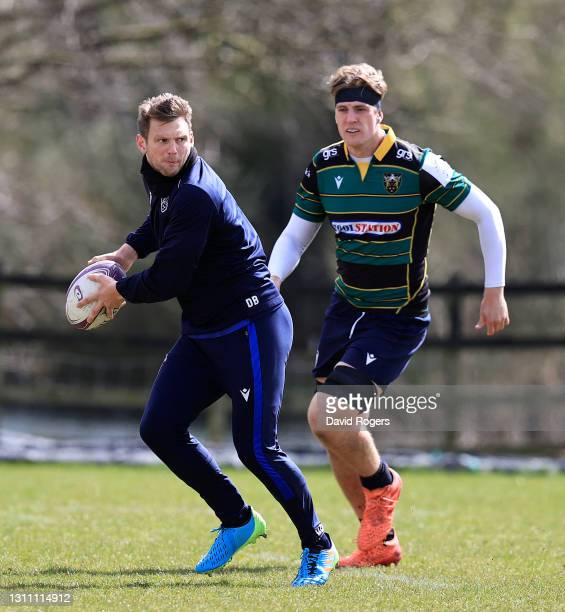 Dan Biggar passes the ball watched by Alex Coles during the Northampton Saints training session held at Franklin's Gardens on April 06, 2021 in...