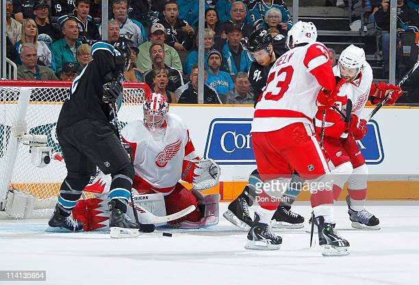 Dan Boyle and Joe Pavelski of the San Jose Sharks look for a rebound against Darren Helm and Jimmy Howard of the Detroit Red Wings in Game Seven of...