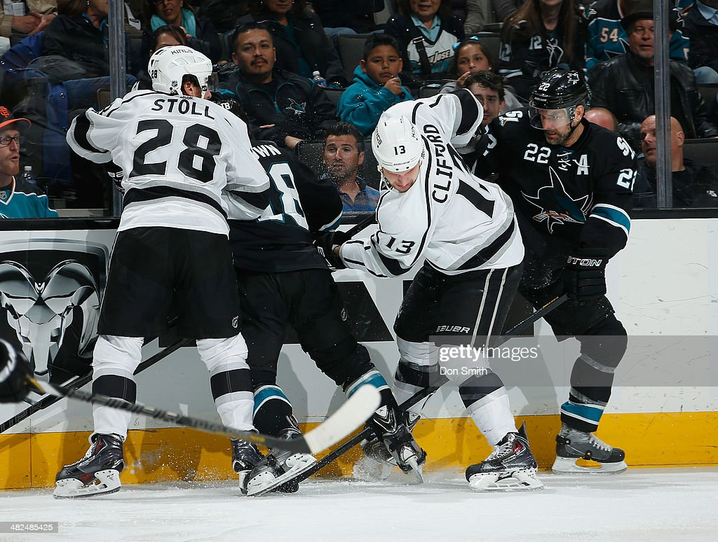 Dan Boyle #22 and Mike Brown #18 of the San Jose Sharks battle for the puck against Kyle Clifford #13 and Jarret Stoll #28 of the Los Angeles Kings during an NHL game on April 3, 2014 at SAP Center in San Jose, California.