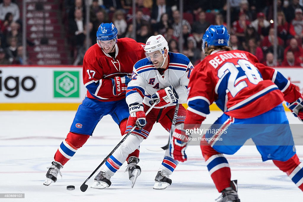 Dan Boyle #22 of the New York Rangers gets the puck past Torrey Mitchell #17 of the Montreal Canadiens during the NHL game at the Bell Centre on October 15, 2015 in Montreal, Quebec, Canada. The Canadiens defeated the Rangers 3-0 and for the first time in franchise history, the Canadiens have won five games in a row to start the season.