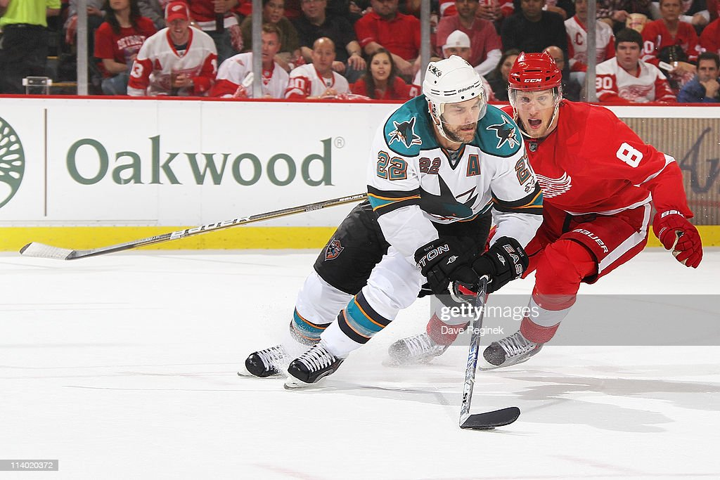 Dan Boyle #22 of the San Jose Sharks carries the puck while Justin Abdelkader #8 of the Detroit Red Wings skates after during Game Six of the Western Conference Semifinals of the 2011 NHL Stanley Cup Playoffs at Joe Louis Arena on May 10, 2011 in Detroit, Michigan. The Detroit Red Wings defeated the San Jose Sharks 3-1.
